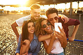 Selfie time! Group of happy young people having fun on shopping trolleys and taking selfie.