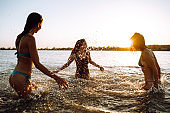 Three young girls splashing water in the sea.