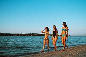 Beautiful three girls strolling along a beach.