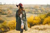 Elegant woman in coat with hat walks in autumn park.