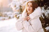 Young beautiful woman posing in a snowy park. Cold weather. Winter fashion, holidays, rest, travel concept.