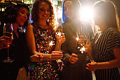 Cheerful women holding sparklers at the party. Celebration, bachelorette party, birthday, winter holidays.