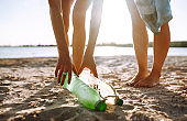Three young girls pick up trash on the beach. Environmental pollution.