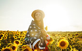 Patriotic girl  in hat with the American flag in a sunflower field at sunset.  Fourth of July. Freedom.