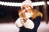 Christmas sparkles in hands. Cheerful young woman celebrating holding sparkles in the winter forest.