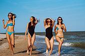 Four girls having fun and running along beach.