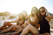 Four girls relax on the beach at sunset.