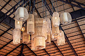 Many local ceiling lamps. Vintage Style Design. Interior of hanging Lamp illuminated, Ceiling light lamp covered with weave , Weave lamps with wooden crafts that come with rhythmic art.