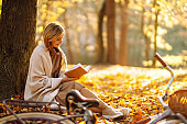 Beautiful young woman sitting on a fallen autumn leaves in a park, reading a book.
