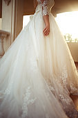 A beautiful bride in a white wedding dress is enjoying the moment on the sunset.