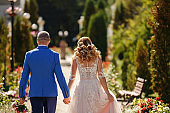 Bride and groom hold hands, walk in park after the wedding ceremony
