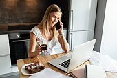 Woman with smartphone and laptop working at home office