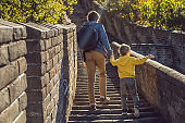 Happy cheerful joyful tourists dad and son at Great Wall of China having fun on travel smiling laughing and dancing during vacation trip in Asia. Chinese destination. Travel with children in China concept