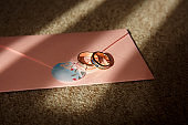 Wedding rings with blue stone on pink wedding invitation