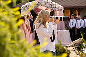 Wedding photographer with a professional camera working at a wedding ceremony