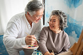 Happy smiling Asian Elderly Couple oil painting on canvas at house.