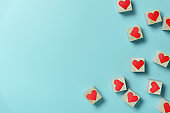 Hearts in Wooden cubes on blue background with copy space.