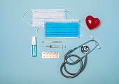 medical equipment stethoscope with red heart and drug, surgical mask on blue background.