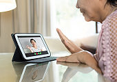 Asian Senior woman waving hand and talking to her relatives and family via internet and wireless technology. Old female making video call from home with digital tablet for meeting with young person during quarantine