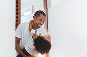 Happy African American hugging with little kid boy on holiday. Black Father and son in white clothes cuddling playing together at home. Love emotion, Family having fun.