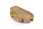 Aerial view of slice of artisan rye bread isolated on white background. Close-up of a piece of freshly baked artisan whole wheat bread. Rustic dark rye sourdough bread in horizontal position