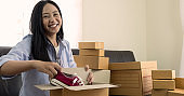 Happy young woman received online shopping parcel opening boxes, she using credit card to buy
