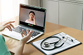 Doctor making video call for talking and consulting with Asian Senior woman Patient about covid 19 or coronavirus symptom with laptop computer at medical room. Internet wireless technology for treatment and meeting