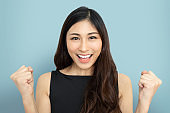 Portrait of beautiful woman in black cloth with victory, winner, success poses. Excited Attractive Asian Businesswoman celebrating with two fists in air on blue isolated background.