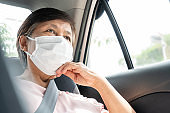 Asian Senior woman Passenger wear surgical mask for prevent and protection coronavirus or Covid-19 while sitting in car. Public transportation. Sanitation, Healthy, Pandemic Virus