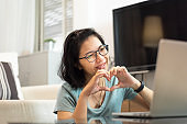 Smiling Asian woman making her hands in heart shape during video call with laptop