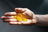 Yellow flaxseed oil in transparent capsules lie in a hand on a gray background. healthy nutritional supplement