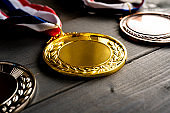Gold and silver bronze medal on wooden table