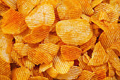 background corrugated golden chips with texture. Food texture. potato chips.Top view. Mock up. Copy space.Template. Blank.