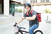 Delivery Man With Bicycle Checking Time On Street