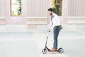 Hispanic male worker riding an eco-friendly scooter