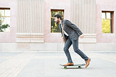 Side view of a man in his 30s wearing a suit and skating to his workplace