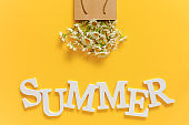 Text SUMMER from white volume letters and field chamomiles flowers in craft package on yellow background. Greeting card Flat Lay Copy space Concept Hello summer, summertime