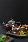 Drink with chaga mushroom in a glass bowl and teapot on a black background. Organic healthy infusion with chaga. Vertical orientation.