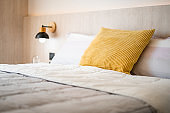 Chic and luxury yellow pillow and white blanket on white oak wooden single bed with bedside hanging lamp in cozy bedroom, Comfy and tasteful bed room design for everyday living of condo, home and apartment, real photo.