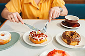 A woman wearing a yellow shirt cut a crispy bacon and cheddar cheese homemade donut with a knife and fork in a modern cafe. Enjoyment female lifestyle.
