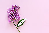 Wooden calendar spring month of May and branch of lilac on pink background. Copy space. Minimal style. Template for greeting card, text, design. Hello May concept
