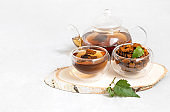 Chaga mushroom drink in glass bowls and teapot on a white background. Healthy infusion with pieces of chaga.