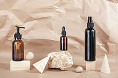 Brown glass bottles of cosmetic products on stone, wooden geometric shapes on beige paper background. Natural Organic Spa Cosmetic Beauty concept Front view Mockup