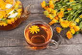Cup of herbal tea and transparent teapot and marigold flowers on wood background. Calendula Tea Benefits Your Health concept
