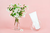 One white blank cosmetic tube bottle and blooming branch in vase on pink background. Natural Organic Spa Cosmetic Beauty Concept. Mockup Front view
