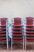 Rows of stacked Dutch pub terrace chairs in front of a white wall in the city of Kampen