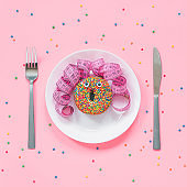 Abstract funny face of woman made donut with eyes and hair from centimeter tape on plate, cutlery on pink background. Fast food, fattening and unhealthy eating creativity concept Top view