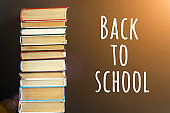 Back to school text on black chalkboard background and stack of books . Concept education. Front view