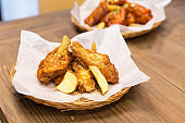 Golden Crunchy Korean Garlic Fried Chicken Wings (basic Huraideu-Chikin) served fried potato with peel. In South Korea, fried chicken is consumed as a meal, an appetizer, Anju, or as an after-meal snack.