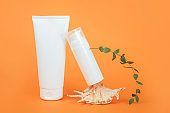 Two white blank cosmetics tube and bottle, sea shell and green eucalyptus branch on orange background. Natural Organic Spa Cosmetic Beauty Concept. Mockup Front view